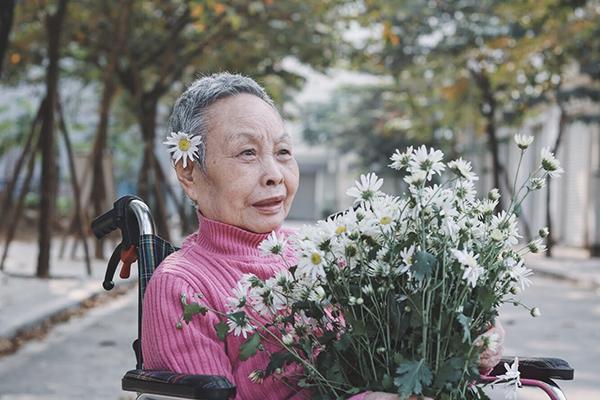Bà Nguyễn Thị Loan, năm nay 82 tuổi, ở trung tâm gần được 2 năm. Các con cháu của bà đều lấy chồng ngoại quốc nên không mấy khi về thăm. Nhân viên trung tâm cho biết, bà Loan giờ trông tiều tụy hơn nhiều, sau một lần bị bệnh phải vào viện hồi năm ngoái. Tuy nhiên, dưới sự chăm sóc tận tình của các bạn điều dưỡng, bà Loan vẫn duyên dáng, tạo kiểu với cái nhìn xa xăm cùng cúc họa mi.